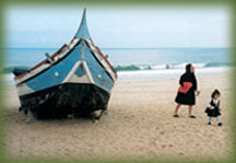 Woman and child near boat on beach